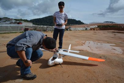 Lian Pin and Ryan preparing drone for launch